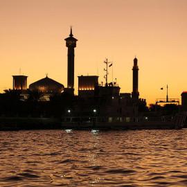 Zachód słońca nad kanałem w Dubai Creek z białym meczetem w tle